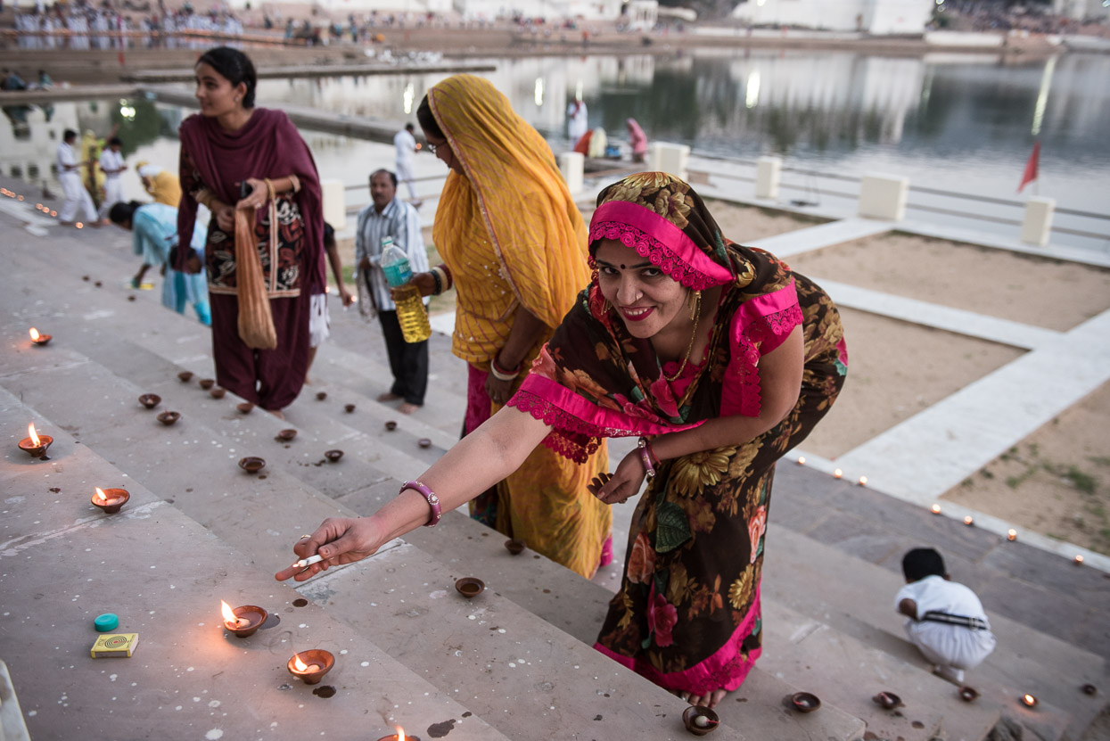 woman lighting a diya in pushkar