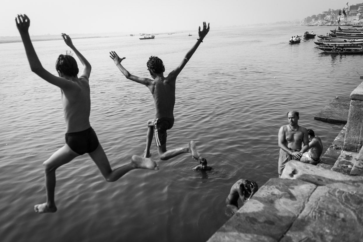 Childrin jumping into the cool waters of Ganges on a hot summer day in Varanasi India