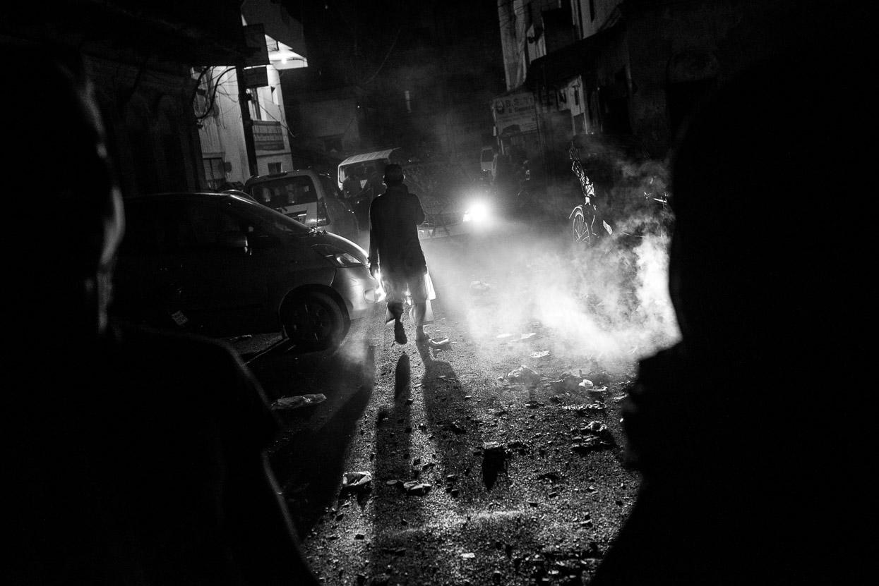 muslim man walking street in Varanasi at night
